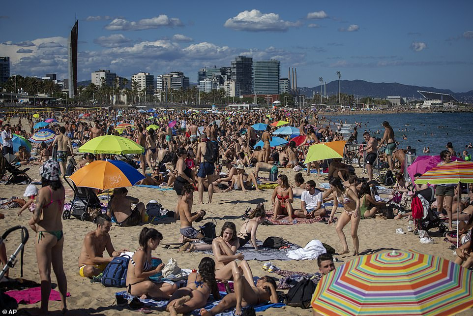 Crowds squeeze on to a beach during comfortable continue in Barcelona, Spain, on Jun 13
