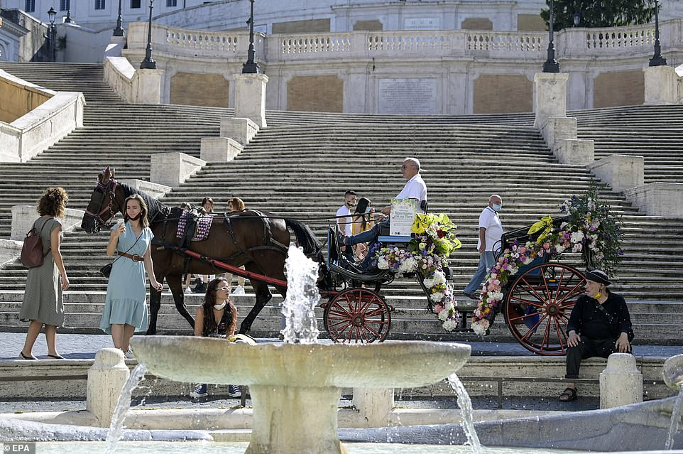 Italy reopened a borders to tourists from Europe during a start of a month, 3 months after they were close as a republic went into coronavirus lockdown. Pictured: eople accumulate around a standard horse-drawn carriage flashy with flowers during Piazza di Spagna in Rome