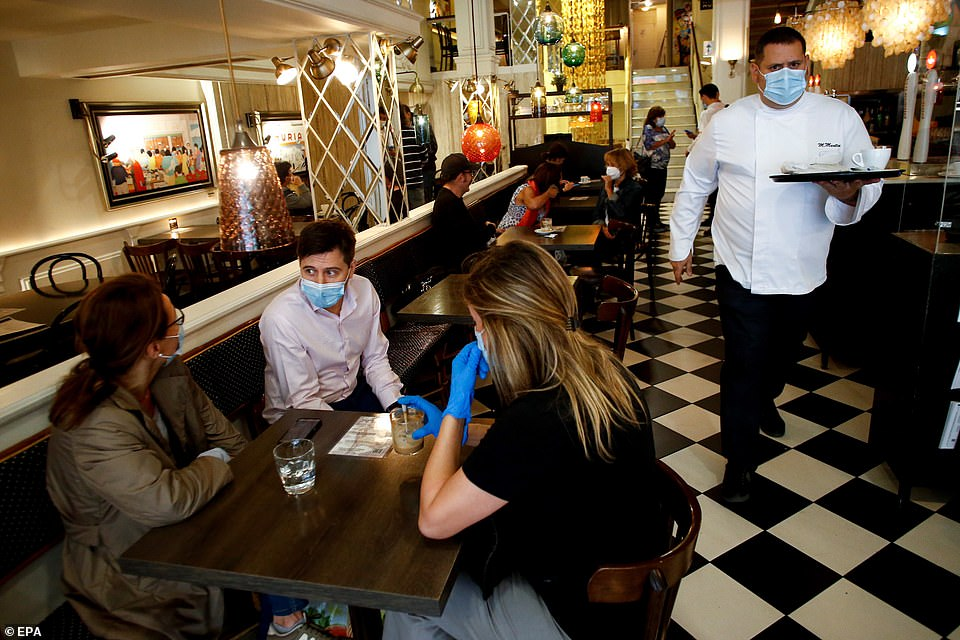 Customers wear face masks as they wait to have breakfast inside a Nuria grill in Barcelona, northeastern Spain progressing this month