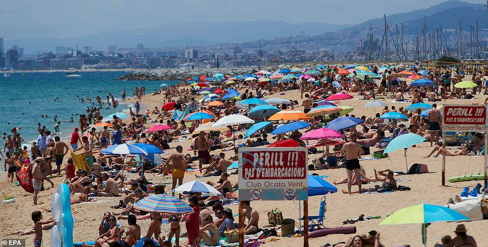 Travel companies have reported their biggest Saturday sales ever as discount hunters rushed to book before a 'traffic light system' is denounced on Wednesday (pictured: beaches are jam-packed on a beach of Calella in Barcelona on Jun 20)